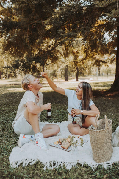 How to Spice Things Up in The Bedroom in 2021. Girlfriend feeds grapes to boyfriend as they have an outdoor picnic.