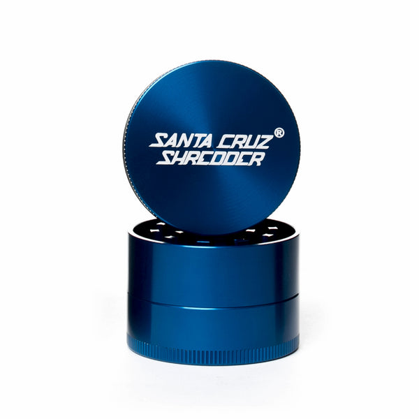 Blue circular 2 piece herb grinder with the lid section sitting on top of the base. Santa Cruz logo on lid.