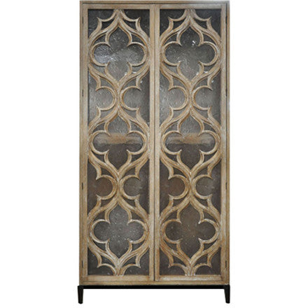 Oly Studio Delphine Tall Cabinet is a hand-carved wood armoire with two doors backed in clear-seeded resin and an antiqued bronze or silver metal base.