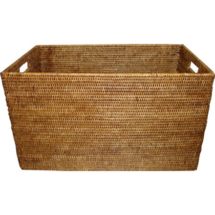Antique brown woven rattan rectangular laundry basket with cutout handles.
