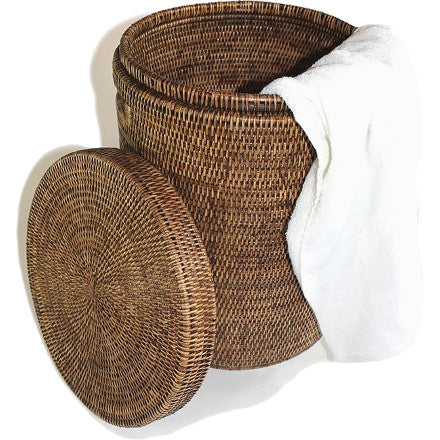 Small round antique brown woven rattan laundry hamper with cutout handles and a lid.