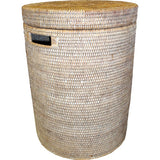 Small round white wash woven rattan laundry hamper with cutout handles and a lid.