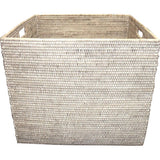 Square white wash woven rattan laundry basket with cutout handles.