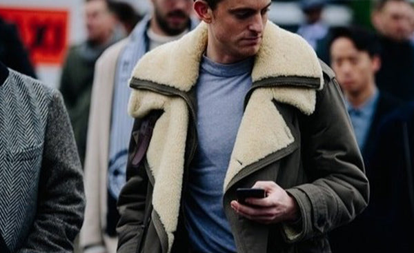 man standing in street in sheepskin jacket