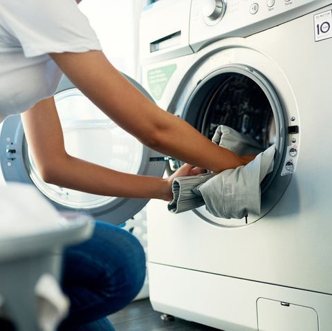 Woman loading washing into the machine