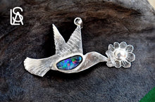 Pendant in the shape of a hummingbird feeding on a flower. Hummingbird's body showcases a black opal in shades of blue, green, and pink.