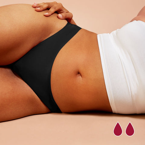 Woman wearing seamless black period underwear laying on her side