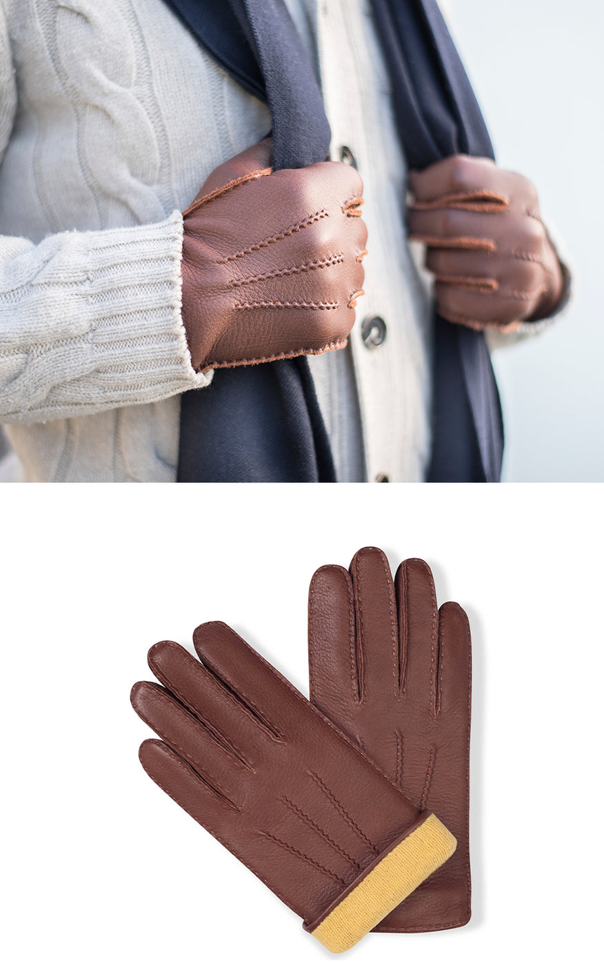 Man in white cardigan wears blue scarf and chestnut brown leather gloves with yellow lining