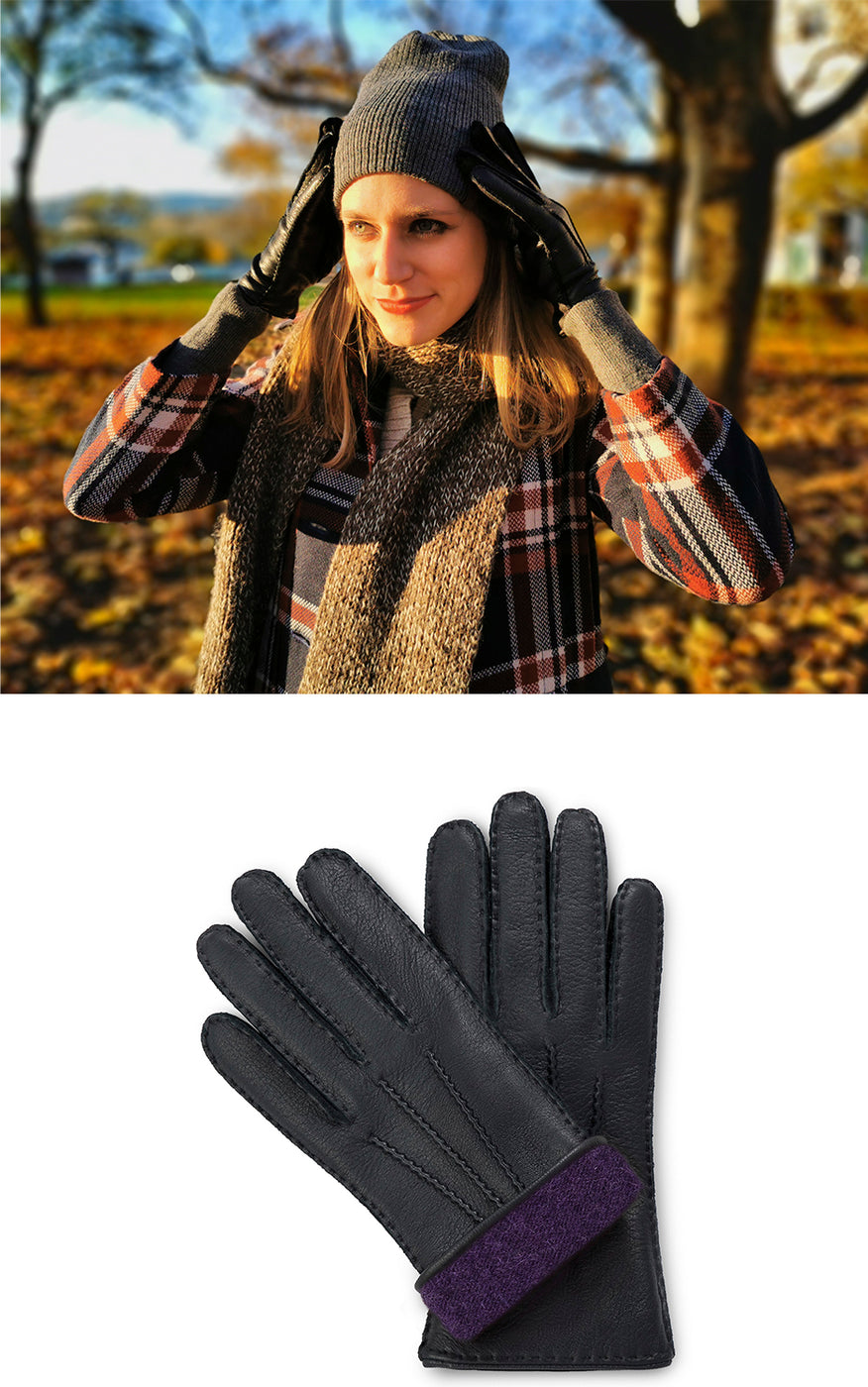 Woman in checked coat wears cap and black moose leather gloves