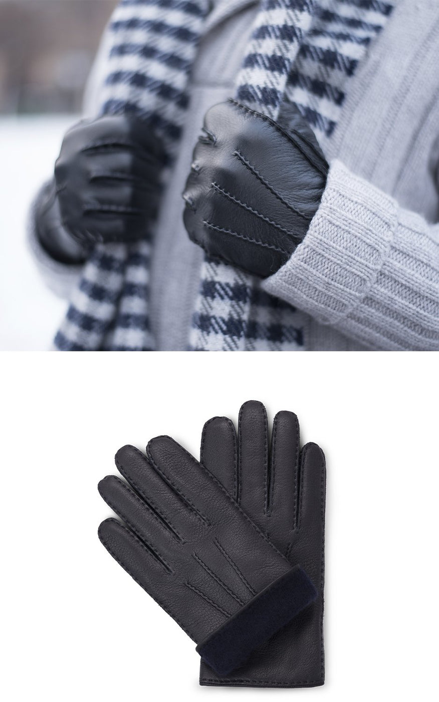 Man in grey sweater wears checked scarf and black moose leather gloves