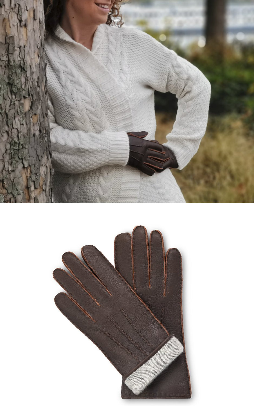 Woman in white cardigan wears dark brown leather gloves