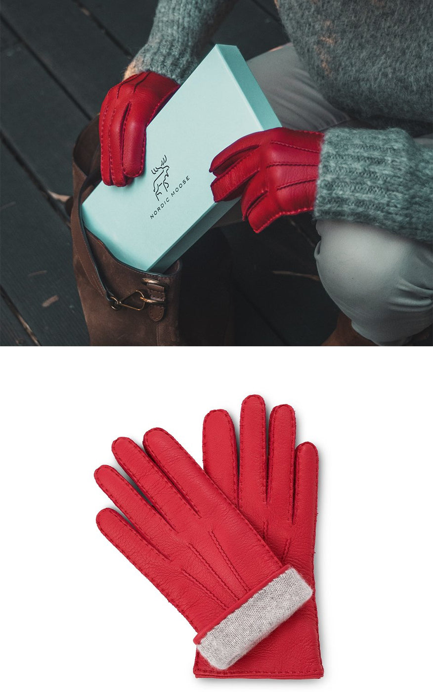 Woman in sweater and red leather gloves put a gift box into her bag