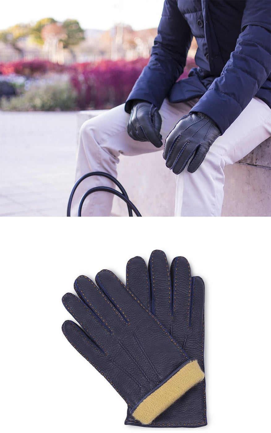 Man in white pants and blue coat wears navy blue leather gloves with yellow cashmere lining