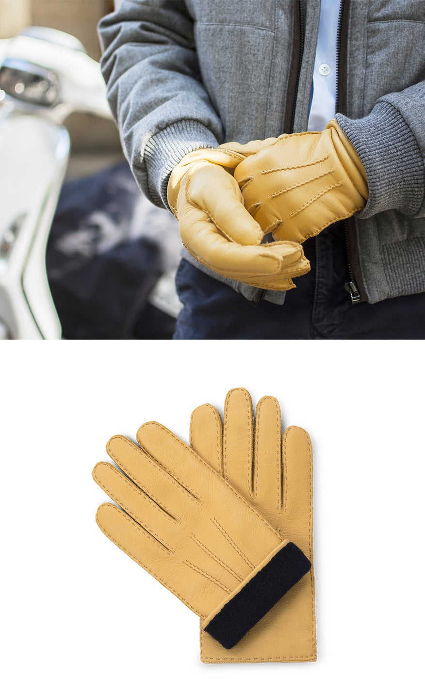 Man in grey coat wears yellow leather gloves with navy blue lining