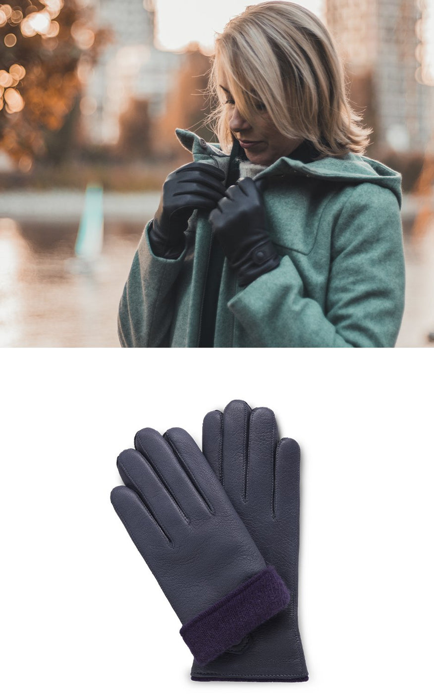 Woman in green coat wears navy blue moose leather gloves with purple cashmere lining
