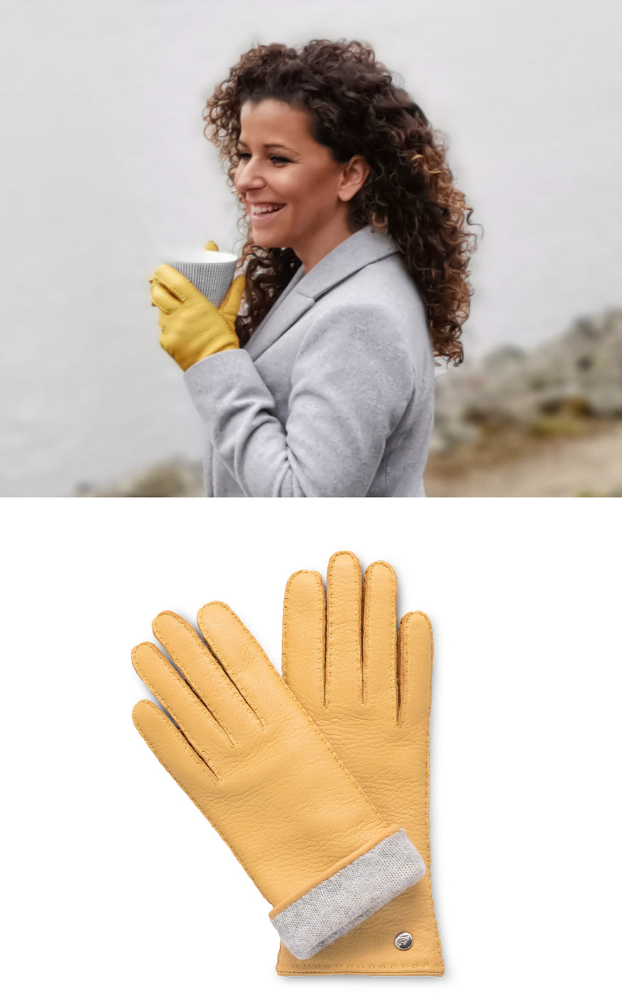 Woman in grey coat drinks from a mug and wears yellow leather gloves