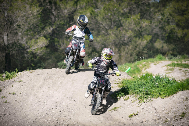 Kids racing an electric motorcycle the Kuberg Cross X Pro 50. Motocross electric bikes.
