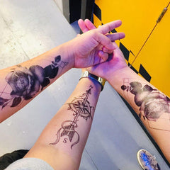 three arms crossed to each other while showing their tintak temporary tattoos on each arm.
