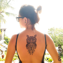 Load image into Gallery viewer, Woman on the beach with owl temporary tattoo on her back.
