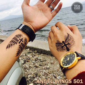 Two men, showing their hand with a temporary tattoo on the beach with winged cross design.