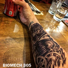 Load image into Gallery viewer, men's arm stretched on top of a wooden table with biomechanical temporary tattoo  sticker with gears and other machine parts