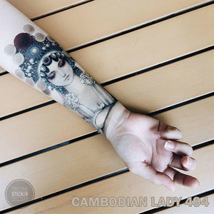 Woman's arm with cambodian lady temporary tattoo on top of a wood slats table.