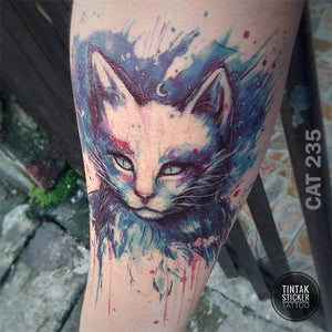 An arm with water-colored cat temporary tattoo.