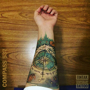 Woman's arm with compass temporaray tattoo design, on top of a wooden table.