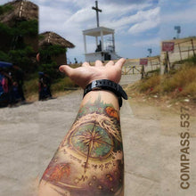 Load image into Gallery viewer, Man's arm with compass temporary tattoo design, with his hand pointing to a cross.