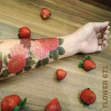 Load image into Gallery viewer, Peony flower temporary tattoo sticker on woman's arm on top of a wooden table with strawberries.