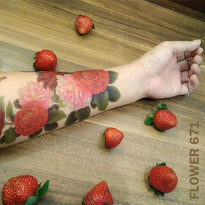 Peony flower temporary tattoo sticker on woman's arm on top of a wooden table with strawberries.