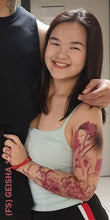Load image into Gallery viewer, Smiling woman with full sleeve temporary tattoo design on her left arm.
