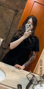 A woman with full sleeve temporary tattoo taking a picture of herself in the mirror.