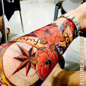 Man's arm with tintak temporary tattoo with compass, flowers, and the eye.