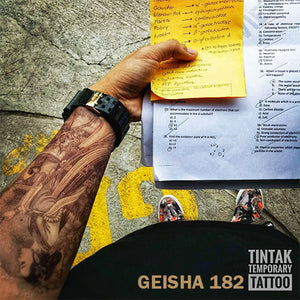 Man's arm with his notes and his geisha temporary tattoo.