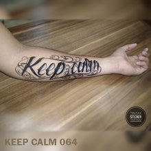 "Load image into Gallery viewer, Man's arm on top of a wooden table with ""Keep Calm"" temporary tattoo design."