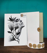 Load image into Gallery viewer, Tintak temporary tattoo sticker with a woman's face and flower design, with its hard board packaging.