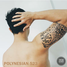 Load image into Gallery viewer, A man on his back, holding his head with his right hand with a polynesian temporary tattoo on his arm.