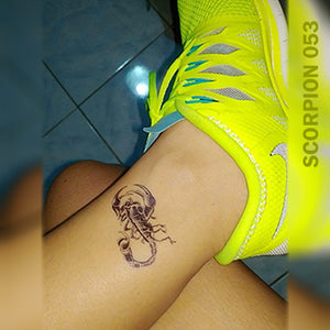 Woman's foot with scorpion temporary tattoo above her neon shoes.