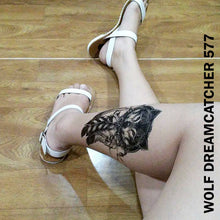 Load image into Gallery viewer, Legs of a woman sitting on the floor while showing her temporary tattoo  sticker on the left with wolf dream catcher design.