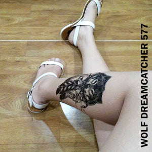 Legs of a woman sitting on the floor while showing her temporary tattoo  sticker on the left with wolf dream catcher design.