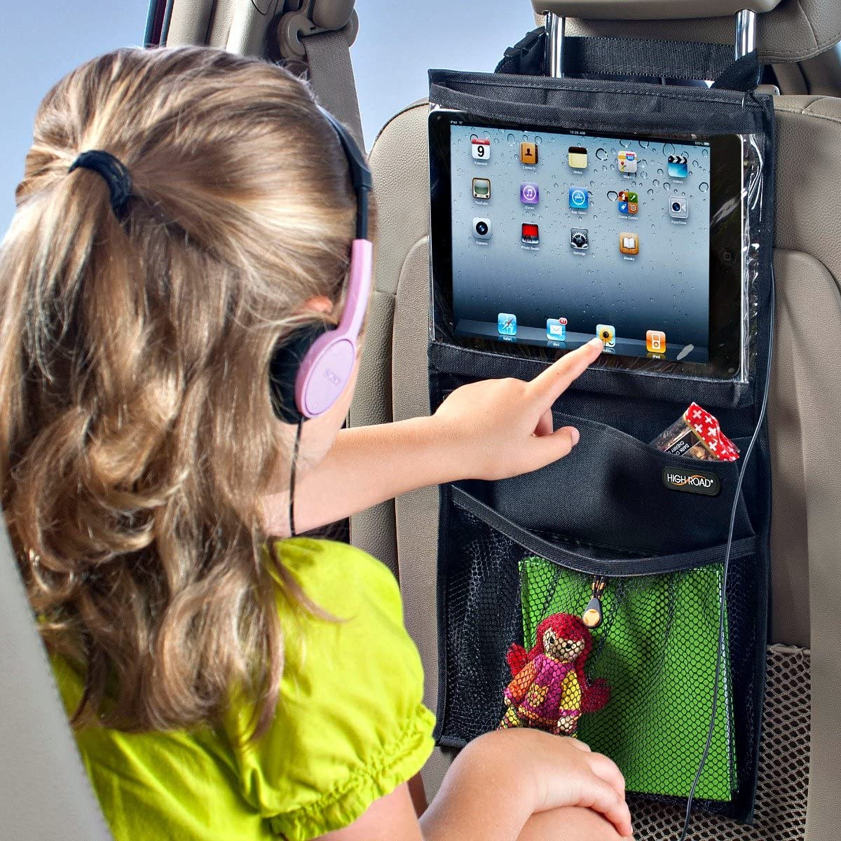 Image showing product mounted behind the drivers seat of a vehicle with a young girl touching icons displayed on the product screen.