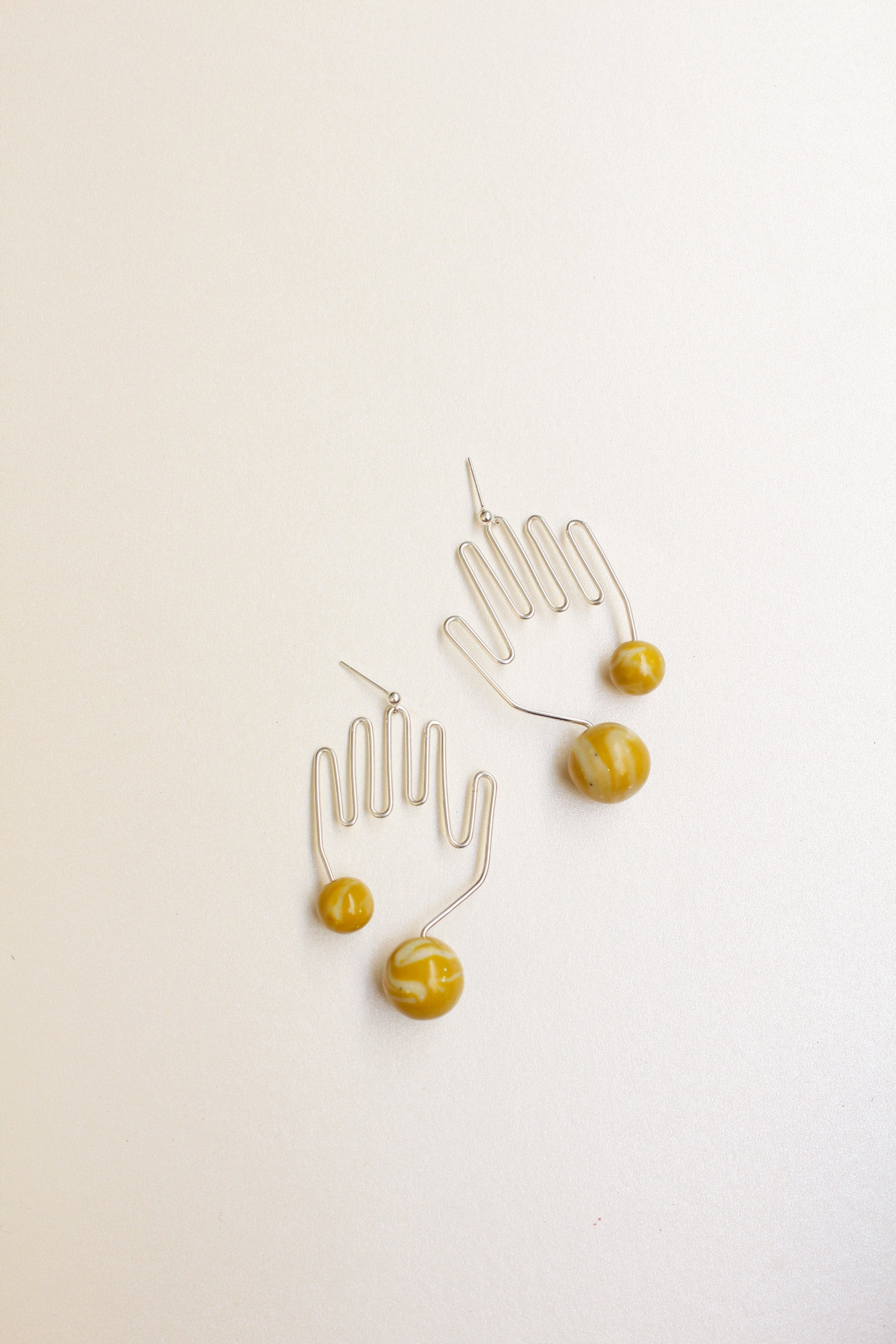 Hand shaped Tsunja Silhouette Earrings with mustard polymer clay beads