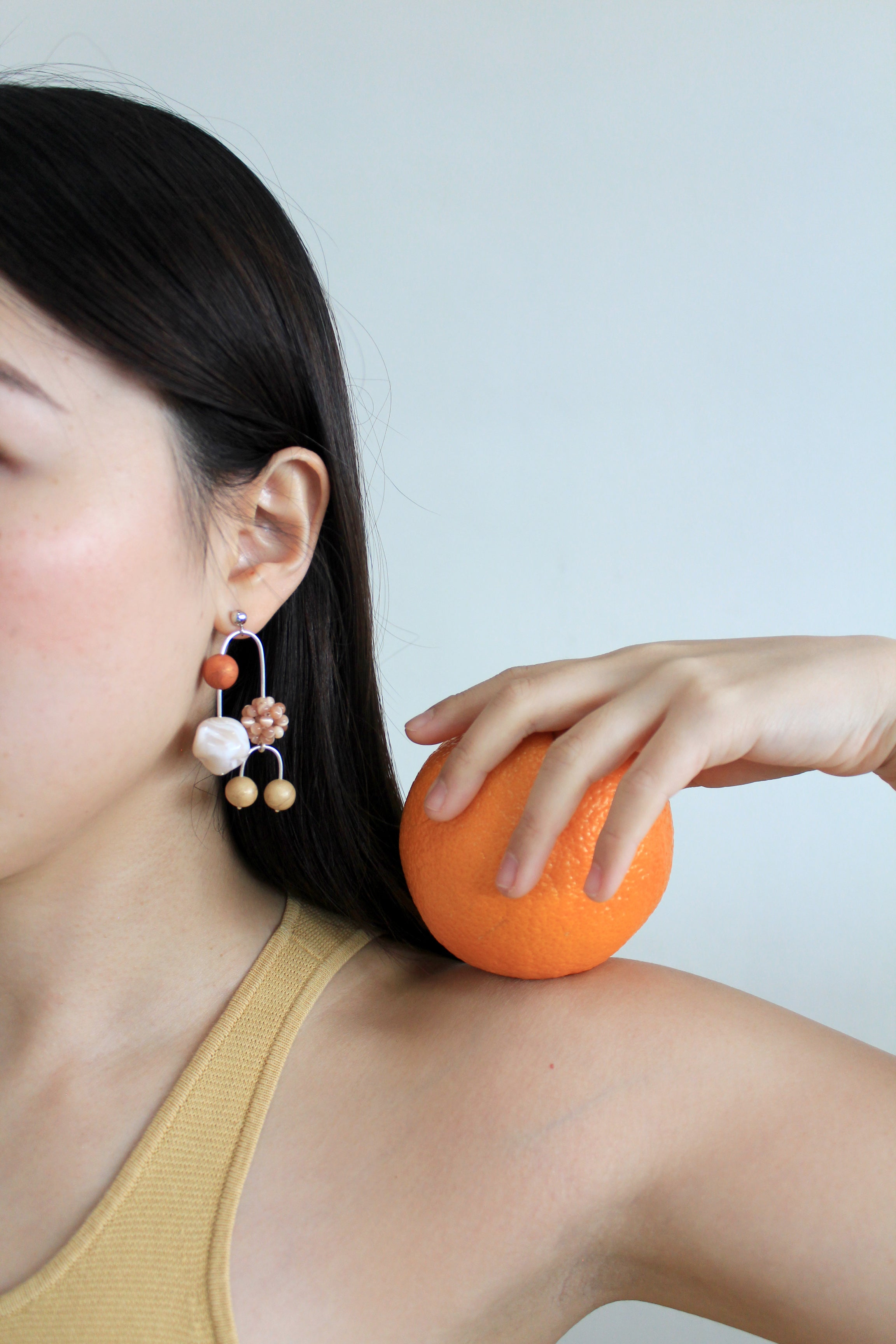 Model wearing Tsunja mobile earrings with polymer clay beads and cat eye beads, Otto Asymmetrical Earrings