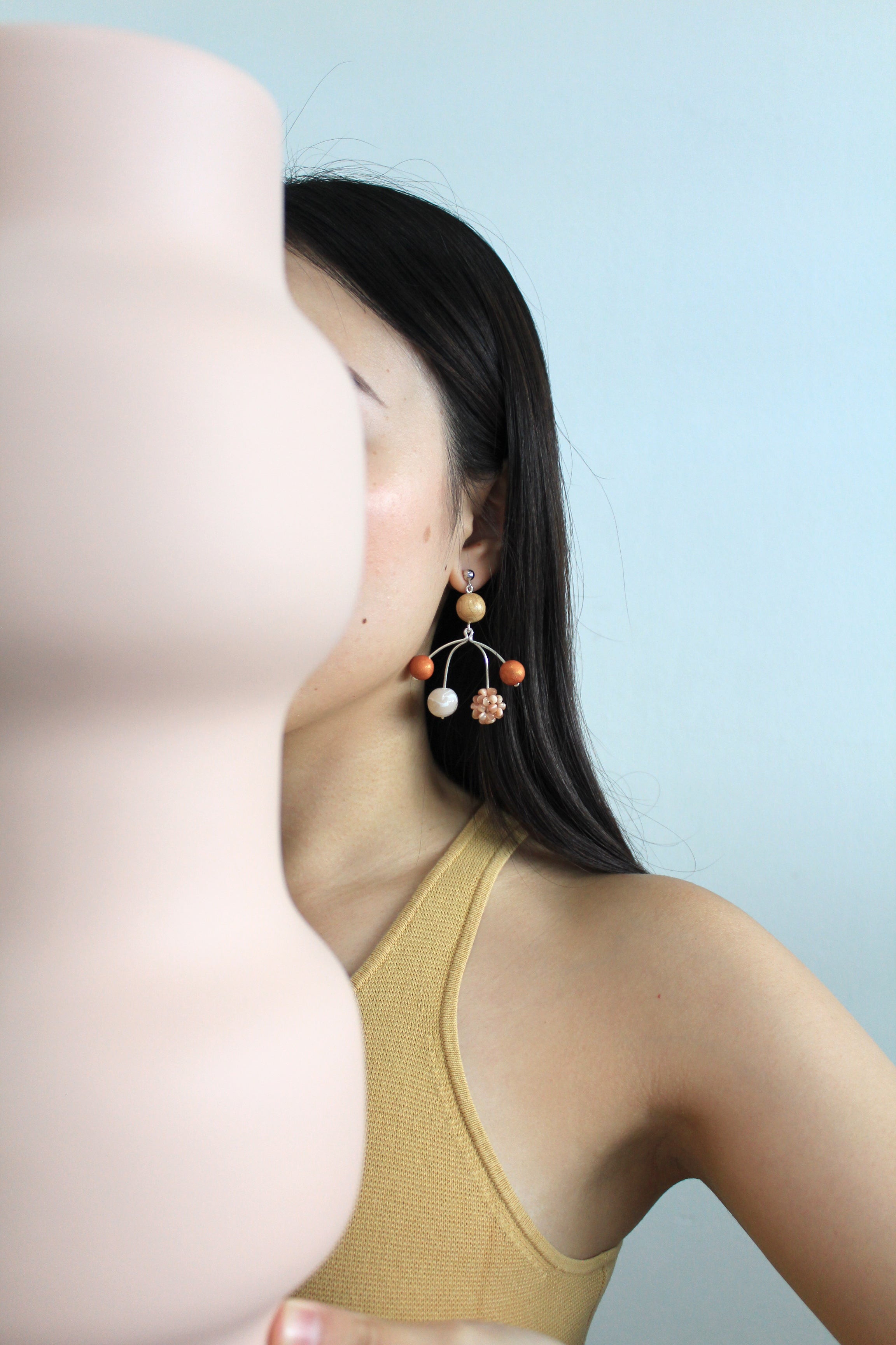 Model wearing Tsunja Mobile Earrings with polymer clay balls and beads in Orange, Otto Earrings