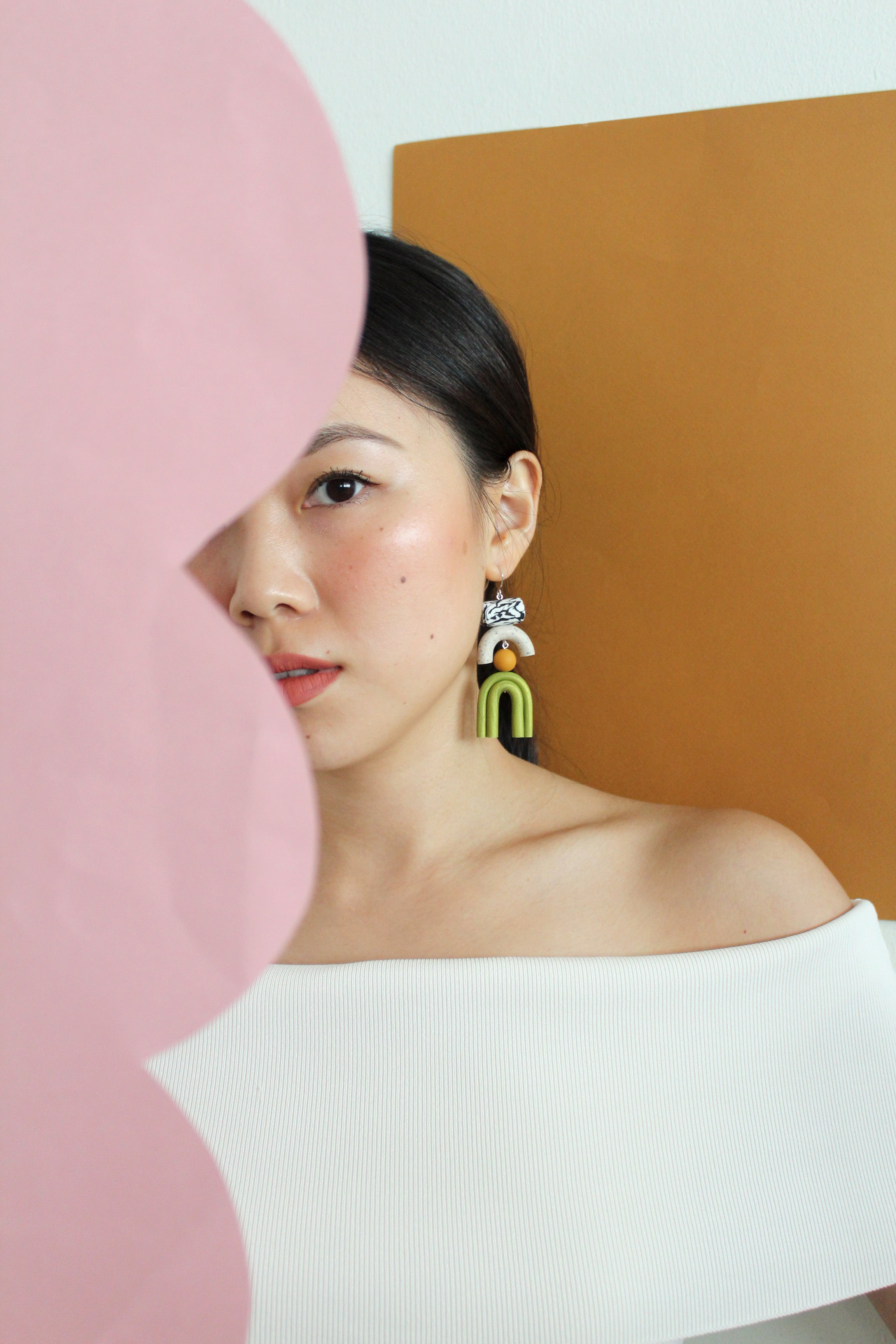 Tsunja polymer clay earrings on model, Bowie earrings in green with silver hook