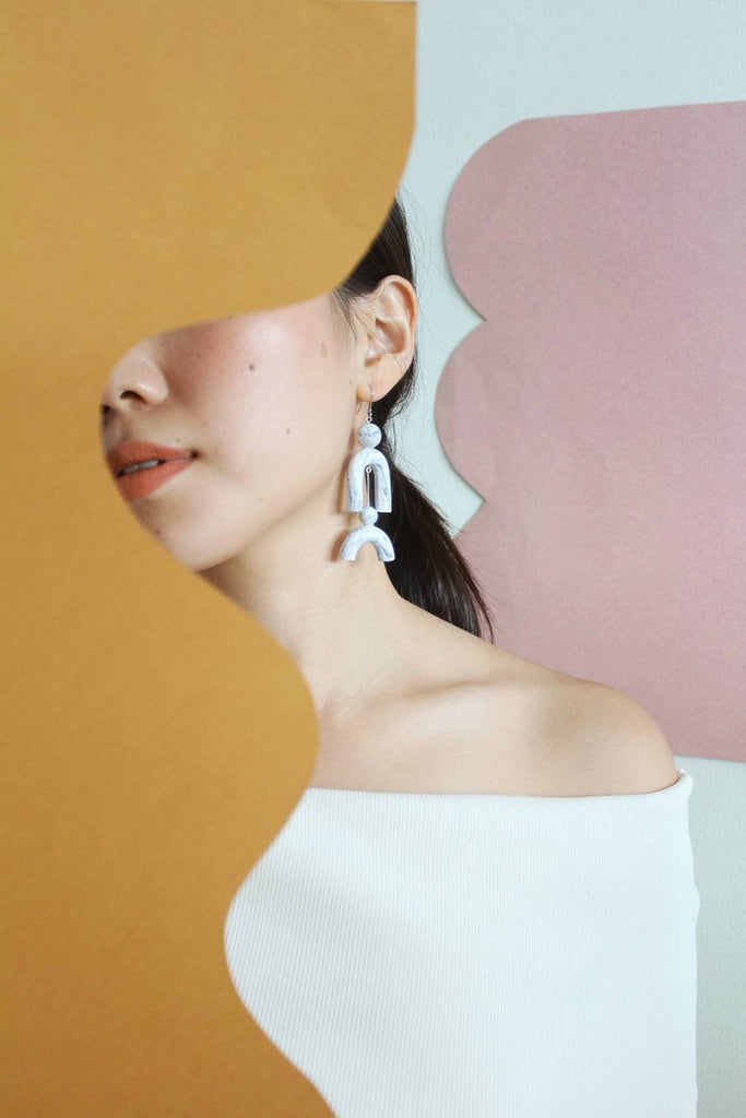Tsunja abstract geometric earrings on model, polymer clay with marble finish