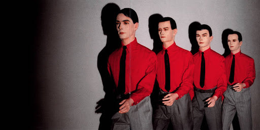 4 male mannequins wearing red shirt grey pants and black tie against a grey background