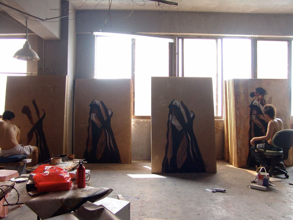 Painters in Dafen paint multiples of one artwork in a sunlit studio. They work barechested and on swivel office chairs