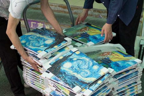 a stack of starry Nights being packaged for shipping in Dafen